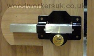 Long throw gate lock postioned on gate