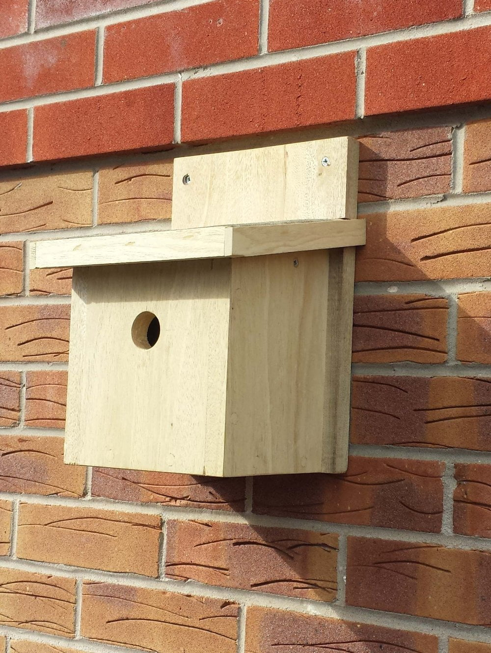 Finished wooden nesting bird box attached to wall